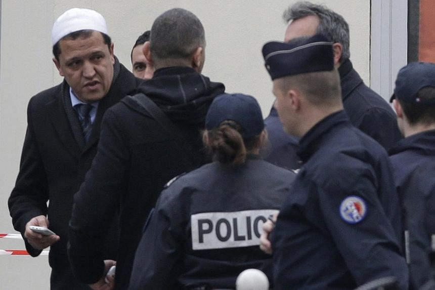 Hassen Chalghoumi (left), Imam of the municipal Drancy mosque in Seine-Saint-Denis, walks with police near the Paris offices of Charlie Hebdo, a satirical newspaper, after a shooting Jan 7, 2015. -- PHOTO: REUTERS