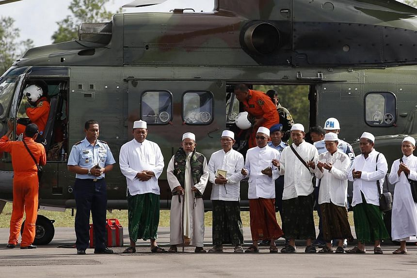 Muslim clerics praying in Pangkalan Bun yesterday before being flown by helicopter to the site where the plane is believed to have crashed. There, they said a prayer for those who lost their lives.