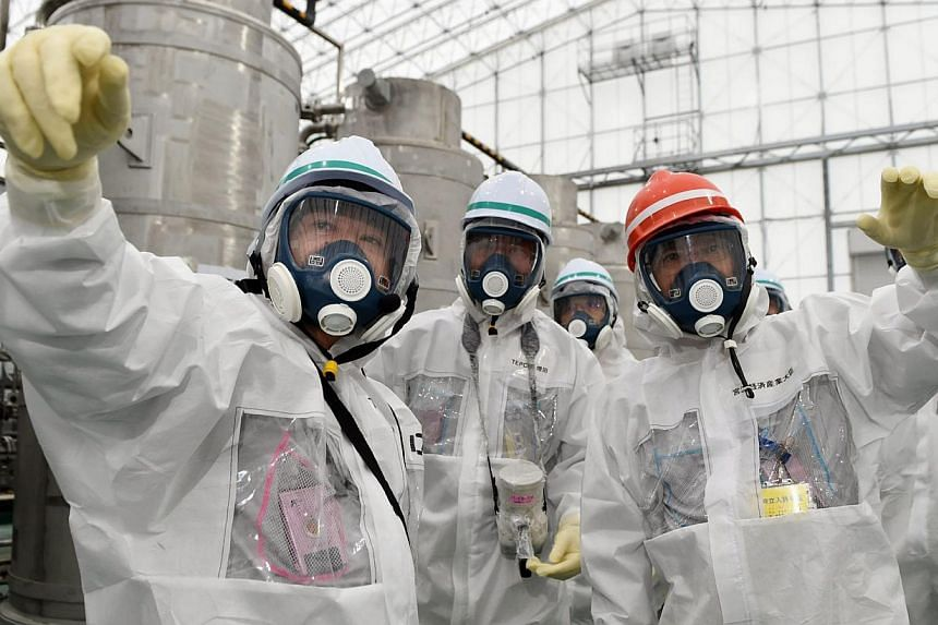 Japan's Economy, Trade and Industry Minister Yoichi Miyazawa (right), wearing a protective suit and mask, inspecings the tsunami-crippled Fukushima Daiichi nuclear power plant in Fukushima prefecture, in a photo released by Kyodo Nov 1, 2014. -- PHOT