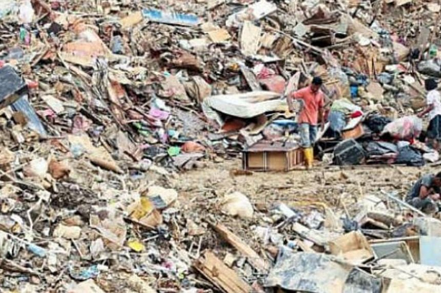 Villagers salvaging useful items from flood trash at an unregistered disposal site in Kuala Krai, Kelantan. -- PHOTO: THE STAR/ASIA NEWS NETWORK
