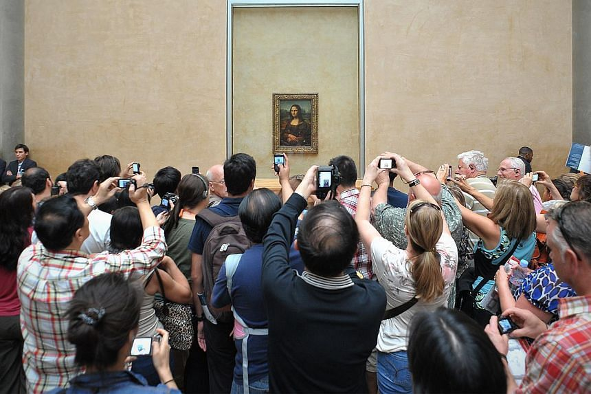 Visitors to the Louvre in Paris take snaps of Leonardo da Vinci's Mona Lisa.The famous Louvre in France received 9.3 million visitors last year, retaining its title as the most-visited museum in the world. -- ST FILE PHOTO