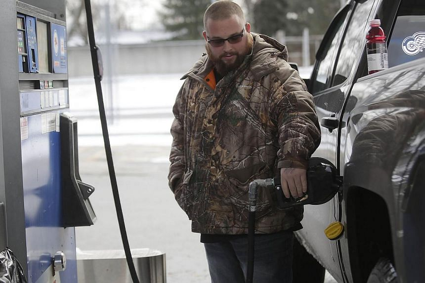 A motorist filling his vehicle with fuel at a Mobil station on Jan 6, 2015 in Livonia, Michigan, in the US. The oil price plunge will force energy companies to slash capital spending in North America, Europe and Asia in 2015, while investment continu