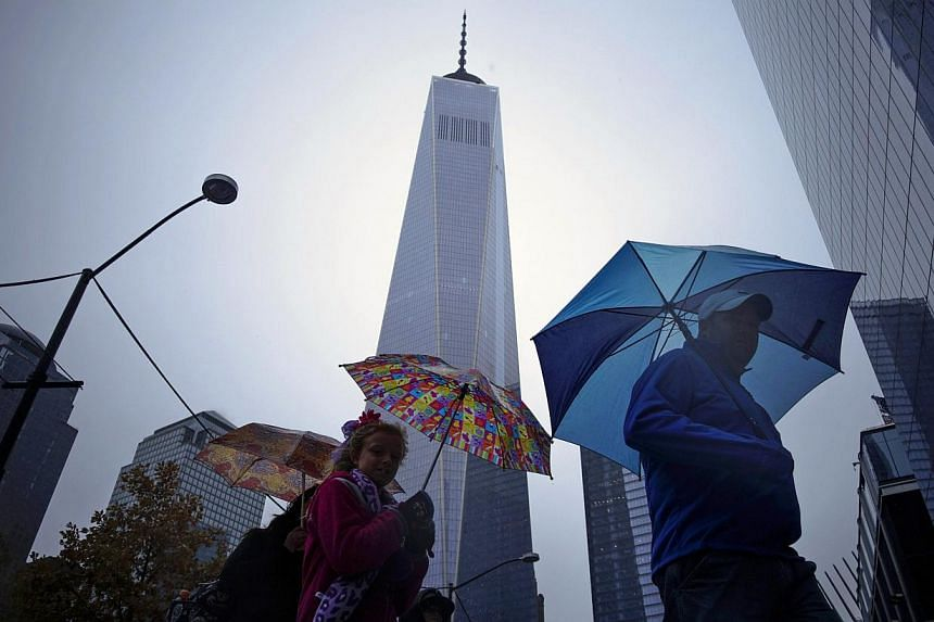 People walking next to the One World Trade Center in New York Nov 1, 2014.  New York City regained its top position among global commercial real estate buyers, unseating London and highlighting the appeal of US properties in general, according t