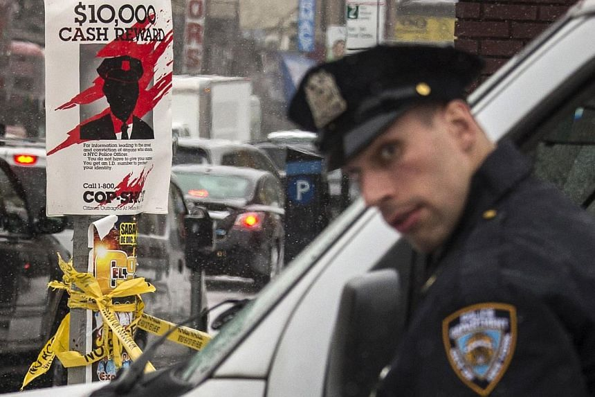 A New York Police Department officer standing next to a sign posted near the site of a shooting in the Bronx borough of New York on Jan 6, 2015. Three people have been arrested for the shooting of two plainclothes officers in the area. -- PHOTO: REUT