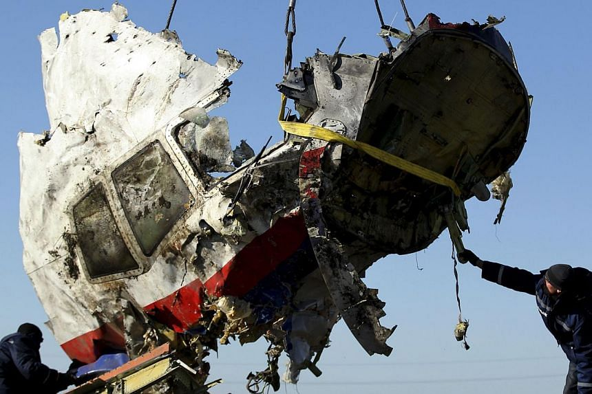 Local workers transport a piece of the Malaysia Airlines flight MH17 wreckage at the site of the plane crash near the village of Hrabove (Grabovo) in the Donetsk region, eastern Ukraine Nov 20, 2014. -- PHOTO: REUTERS