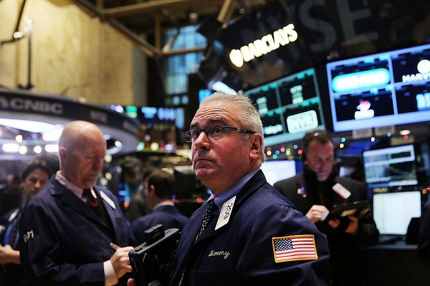 Traders working on the floor of the New York Stock Exchange (NYSE) on Tuesday in New York City. Stocks sank again, partly on fears of a continued fall in global oil prices. -- PHOTO: AFP