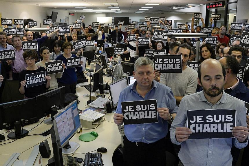 "Journalists with placards reading ""I am Charlie"" observing a minute of silence, on Jan 7, 2015, following the attack by gunmen in the offices of the French satirical weekly Charlie Hebdo. -- PHOTO: AFP"