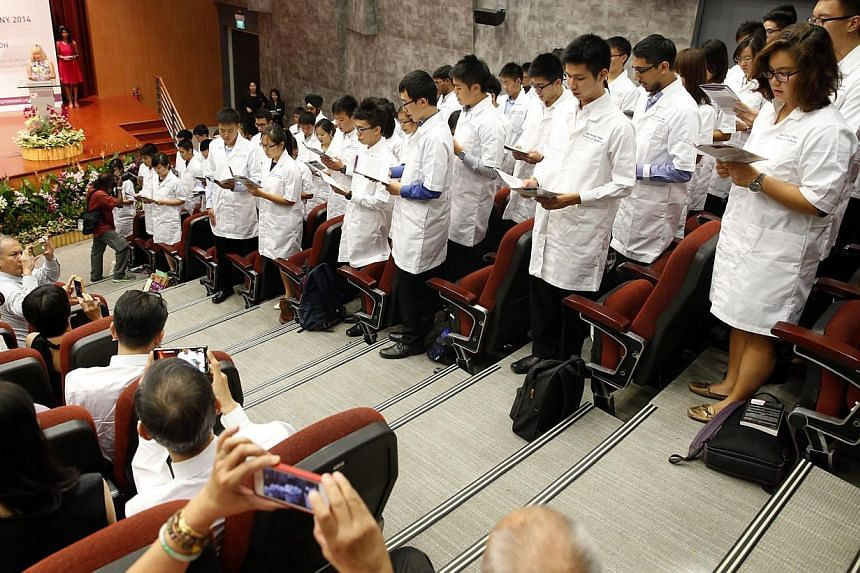 "The second cohort of the Lee Kong Chian School of Medicine reciting the ""Declaration of a new medical student"" at a white coat ceremony at the School of Arts, Design and Media Auditorium in August 2014. -- PHOTO: ST FILE"
