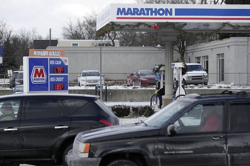 A Marathon petrol station on Jan 6, 2015 in Livonia, Michigan. US crude held above US$48 on Thursday after a surprise drop in inventories. -- PHOTO: AFP