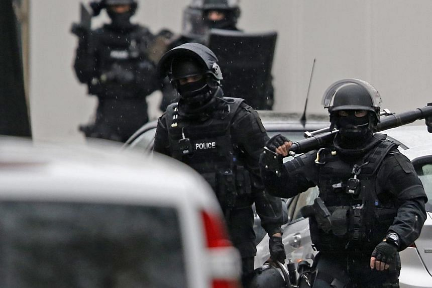 Members of French special police forces of Research and Intervention Brigade (BRI) are seen at the scene of a shooting in the street of Montrouge near Paris on Jan 8, 2015.Two armed suspects of a Paris magazine shooting have been cornered in a