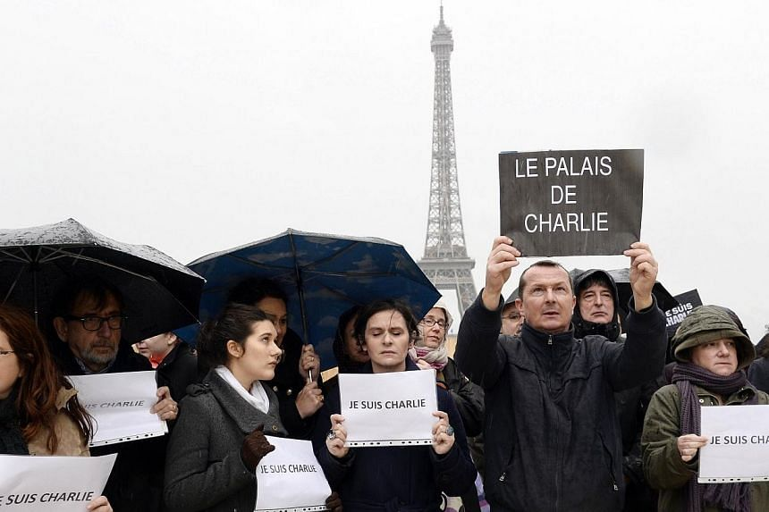 """A man holds a sign reading """"The palace of Charlie"""" as people observe a minute of silence in front of the Eiffel Tower in Paris on Jan 8, 2015, in honour of the 12 people killed by extremists at a magazine known for publishing cartoons deemed offensiv"""
