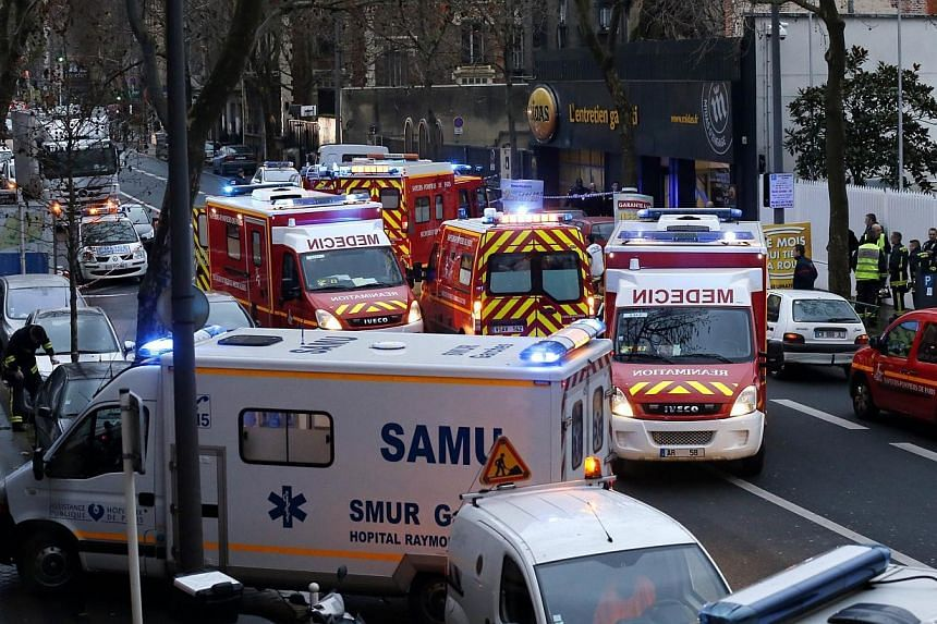 Rescue service workers and firefighters gathering near the site of a shooting on the morning of Jan 8, 2015 in Montrouge, south of Paris. A man wearing a bullet-proof vest fired on police officers with an automatic rifle on Thursday just outside