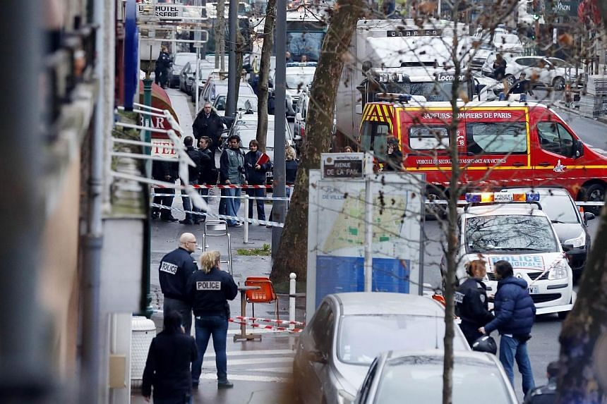 Police and firefighters gathering at the site of a shooting on the morning of Jan 8, 2015, in Montrouge, south of Paris. -- PHOTO: AFP