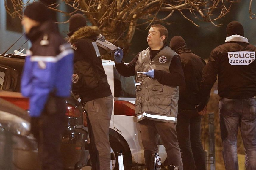 Police investigators search for evidence as an unidentified man is detained (2nd from right) during an operation in the eastern French city of Reims Jan 8, 2015, after the shooting against the Paris offices of Charlie Hebdo, a satirical newspaper.&nb