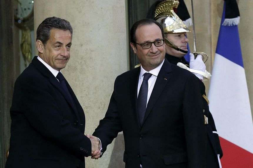 French President Francois Hollande (right) shakes hands with former French President Nicolas Sarkozy, head of the French conservative party UMP party, prior to a meeting at the Elysee Palace in Paris, on Jan 8, 2015, the day after a shooting at the P