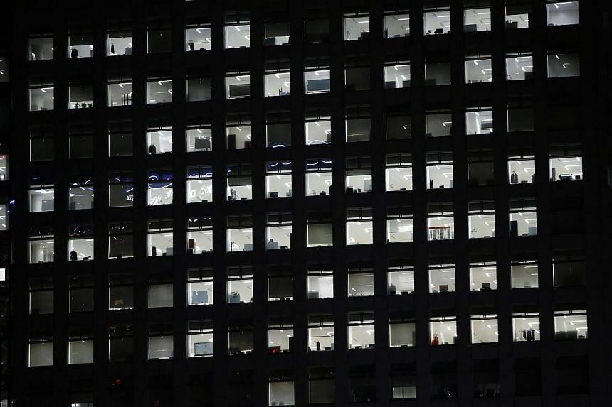 Office lights are seen through the windows of a high-rise office building in Tokyo on July 31, 2014. Japan's government is set to ensure all salaried employees go on paid annual leave by making it the responsibility of their employers, the Yomiu