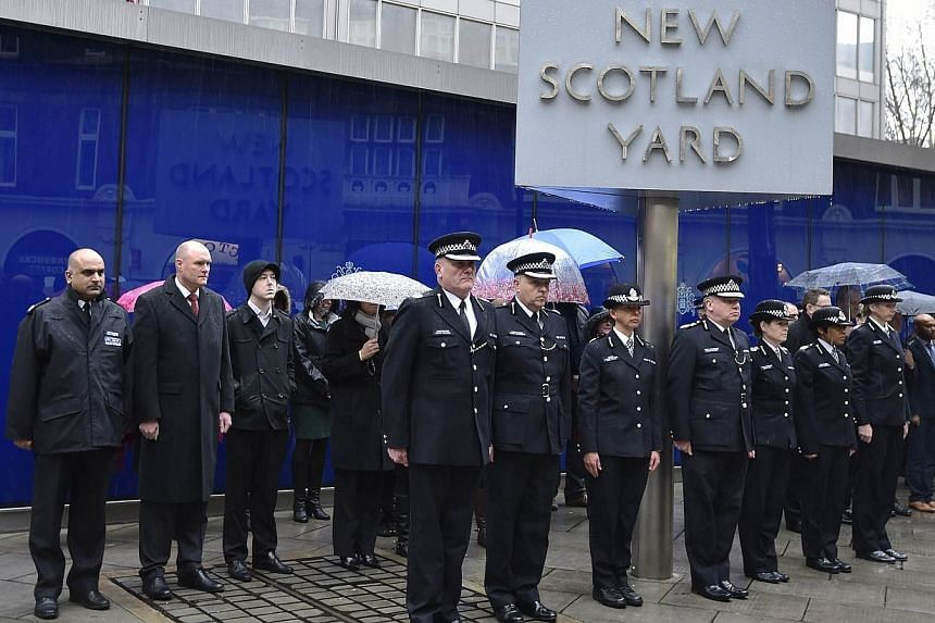 British police officers observe a two minute silence outside the Metropolitan Police headquarters, New Scotland Yard, in central London on Jan 8, 2015.Britain has increased security at some of its borders, including ports and rail entry points,