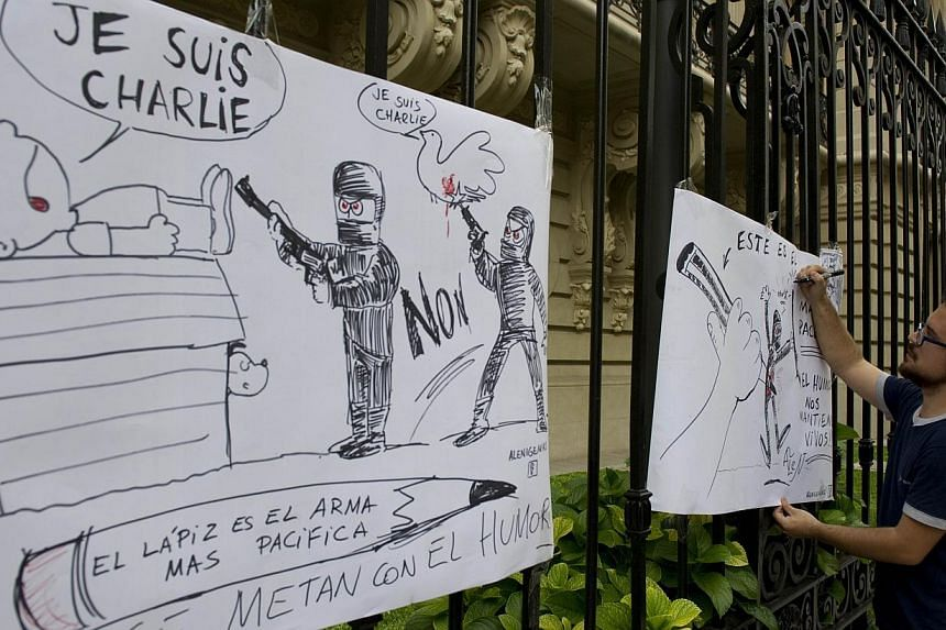 An Argentine cartoonist drawing at the gates of the French Embassy in Buenos Aires on Jan 7, 2015, during a demonstration against the attack on the satirical weekly Charlie Hebdo in Paris. -- PHOTO: AFP