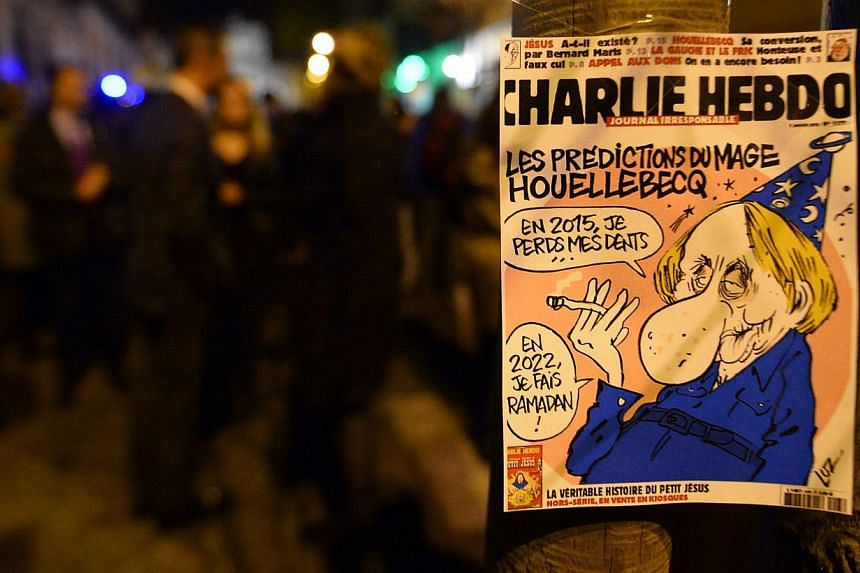The frontpage of last issue of French satirical newspaper Charlie Hebdo is seen during a gathering in support of the victims of the terrorist attack on its Paris offices, in front of the French Embassy in Madrid, on Jan 7, 2015. -- PHOTO: AFP