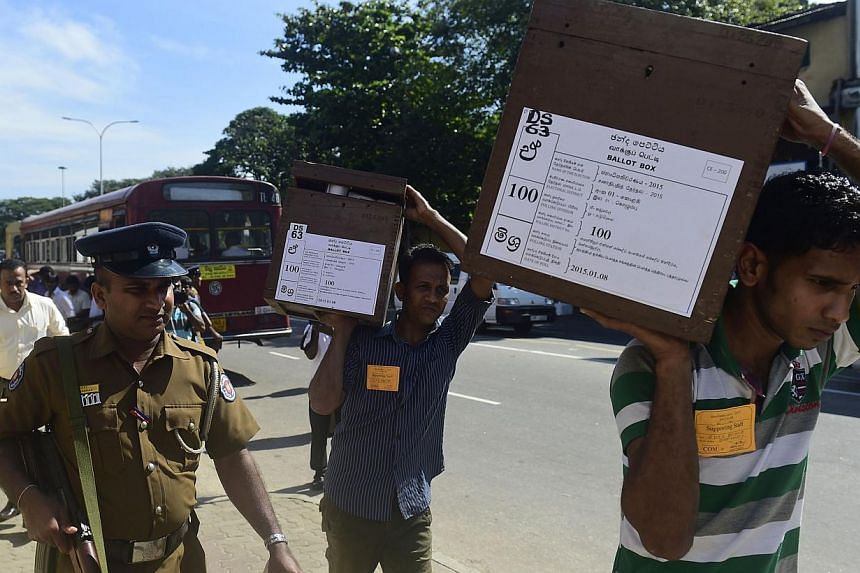 Sri Lankan election commission workers carrying ballot boxes on the eve of presidential elections in Colombo on Jan 7, 2015. -- PHOTO: AFP
