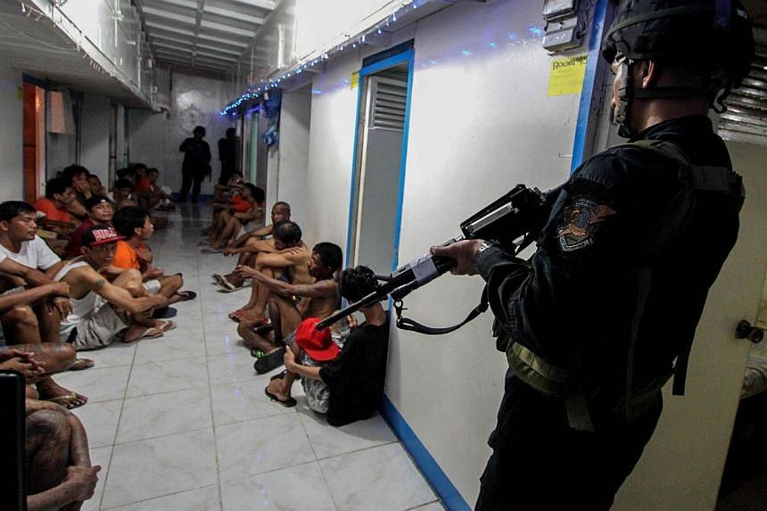 This file photo taken on Dec 16, 2014 shows National Bureau of Investigation (NBI) operatives rounding up inmates inside New Bilibid Prison in Muntinlupa, south of Manila. One inmate was killed and 19 injured in an explosion at a notorious Philippine