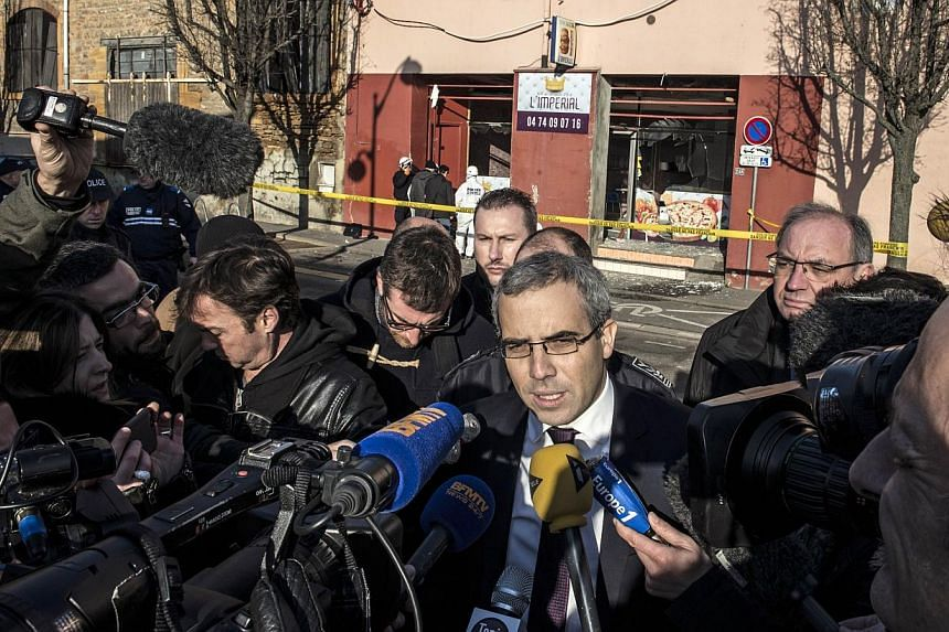 Public prosecutor Gregoire Dulin speaks to journalists as French police forensic (background) scour the scene of an explosion at a kebab shop damaged following an explosion near a mosque, on Jan 8, 2015, in Villefranche-sur-Saone, eastern France. --