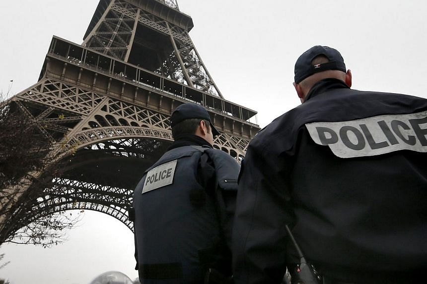 French police patrol near the Eiffel Tower in Paris after a shooting at the Paris offices of Charlie Hebdo on Jan 7, 2015. There are unconfirmed media reports that one of the suspects of the shooting has been killed by police and the other two taken