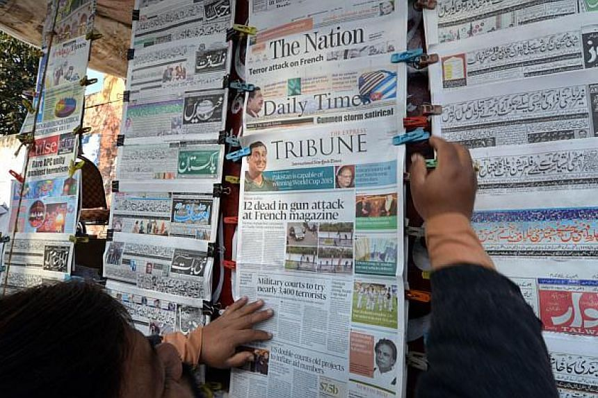 A Pakistani vendor arranging morning newspapers with front-page-coverage of the attack by gunmen on French satirical weekly Charlie Hebdo in Paris, at a roadside newsstand in Islamabad on Jan 8, 2015. -- PHOTO: AFP