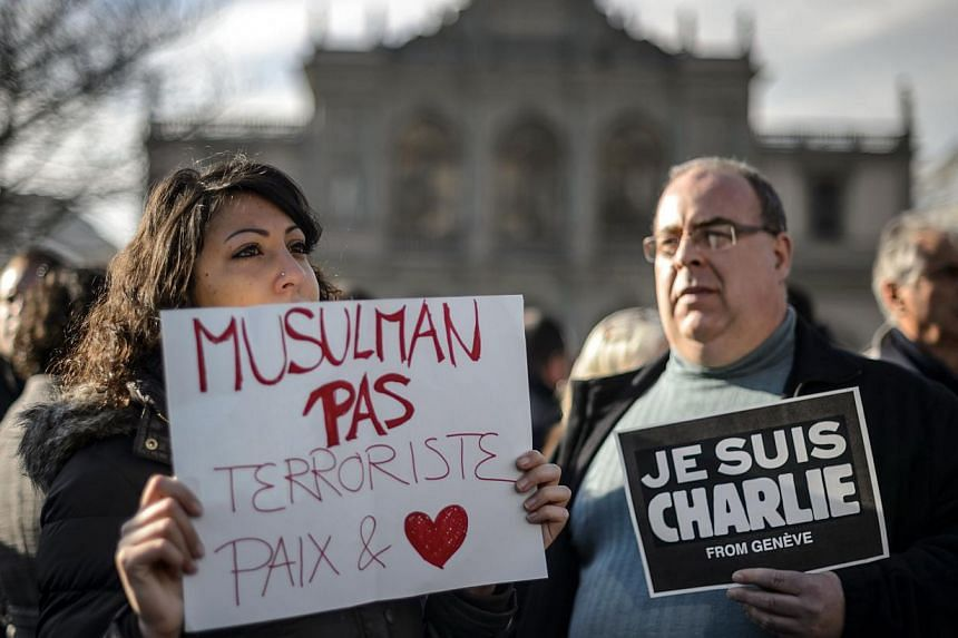 "People hold placards reading in French ""Muslim not terrorists, peace and love"" and ""I am Charlie from Geneva"" (right) during a gathering in the centre of Geneva on Jan 8, 2015 to pay tribute to the 12 people killed the day before in an attack by arme"