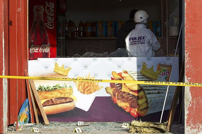 A police investigator inspects the scene after an attack at a kebab restaurant near el Houda mosque in Villefrance-sur-Saone near Lyon on Jan 8, 2015, the day after a shooting at the Paris offices of satirical magazine Charlie Hebdo. -- PHOTO: REUTER