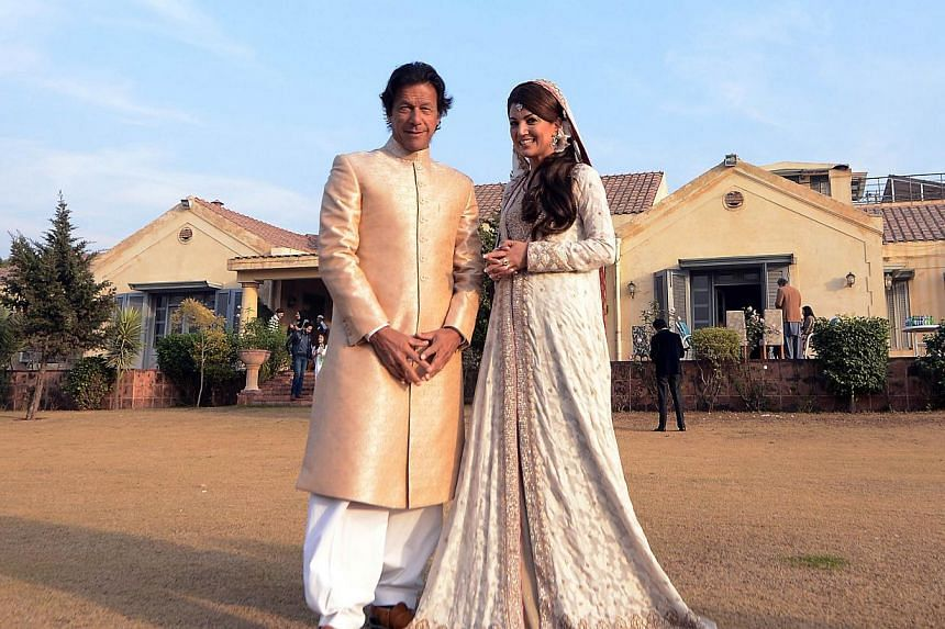 In this handout photograph released by the Pakistan Tehreek Insaf (PTI) party on Jan 8, 2015, Pakistani opposition leader Imran Khan (left) and new wife Reham Khan pose for a photograph during their wedding ceremony at his house in Islamabad. -- PHOT