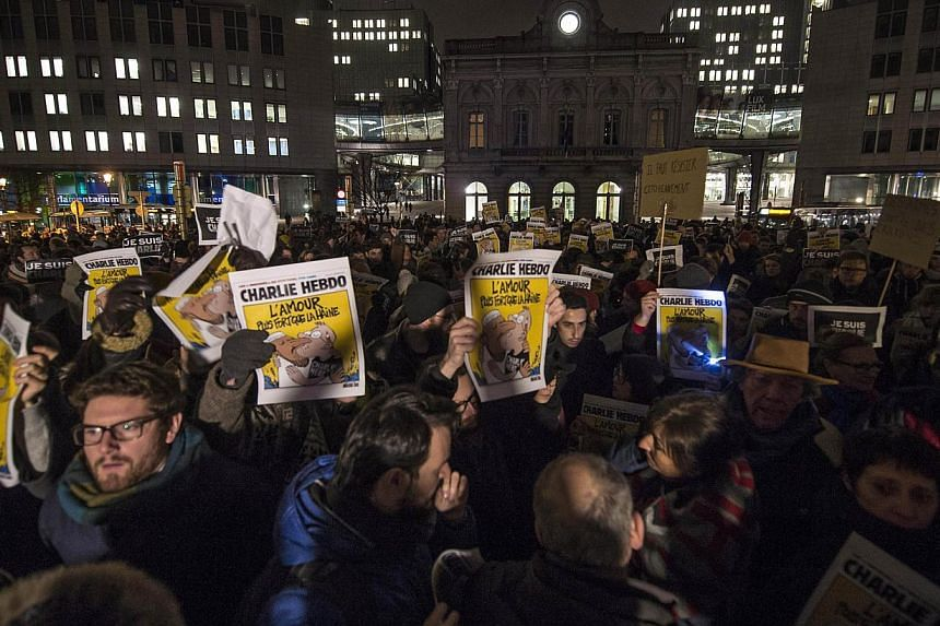 People gatheingr in Brussels, Belgium, on Jan 7, 2015, to show their solidarity for the victims of the attack by unknown gunmen on the offices of the satirical weekly, Charlie Hebdo. -- PHOTO: AFP