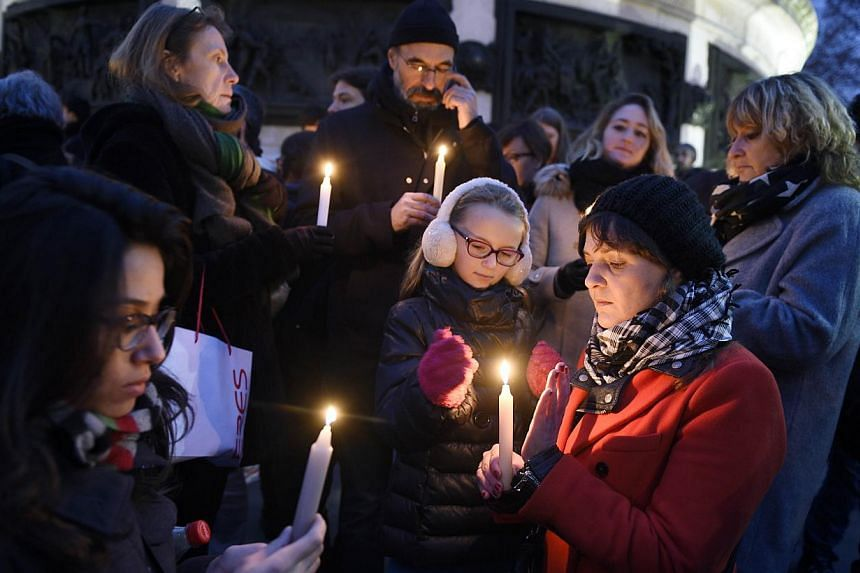People lighting candles during a rally in support of the victims of the attack by gunmen at French satyrical newspaper Charlie Hebdo at the Place de la Republique in Paris, on Jan 7, 2015. -- PHOTO: AFP