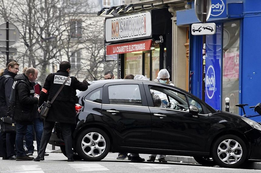 French police officers and forensic experts examine the car used by armed gunmen who stormed the Paris offices of satirical newspaper Charlie Hebdo, killing 12 people, on Jan 7, 2015 in Paris. -- PHOTO: AFP