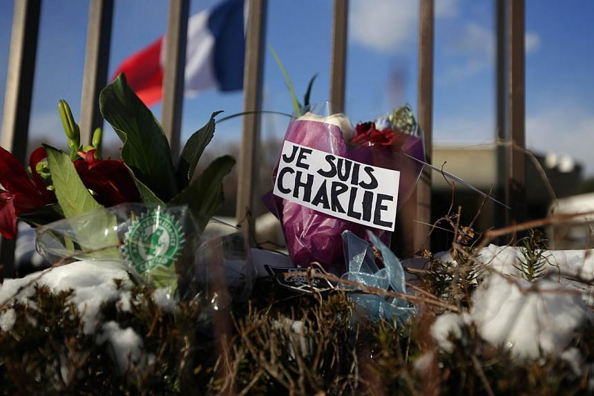 Flowers placed at in the French Embassy in Washington, DC on Jan 7, 2015, in tribute to victims of the attack on satirical magazine Charlie Hebdo in Paris. -- PHOTO: AFP