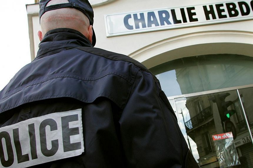 """A policeman stands guard outside the French satirical weekly """"Charlie Hebdo"""" in Paris on Feb 9, 2006. -- PHOTO: REUTERS"""
