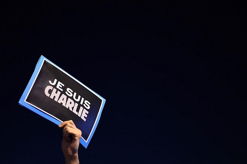 "A man holds a placard reading ""I am Charlie"" on the Old Harbor in Marseille, southern France, on Jan 7, 2015, following an attack by unknown gunmen on the offices of the satirical weekly, Charlie Hebdo. -- PHOTO: AFP"