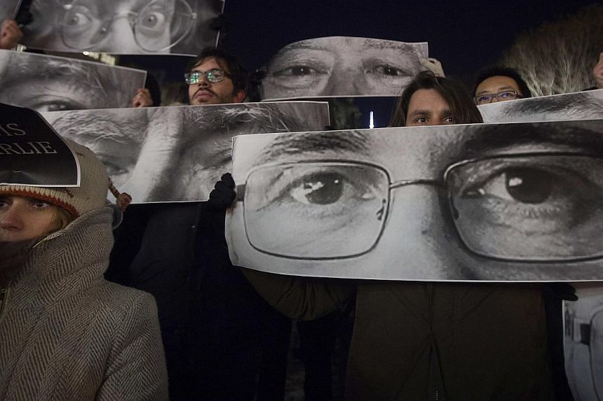 People holding up posters during a vigil to pay tribute to the victims of the attack on weekly satirical magazine Charlie Hebdo in Paris, in the Manhattan borough of New York on Jan 7, 2015. -- PHOTO: REUTERS