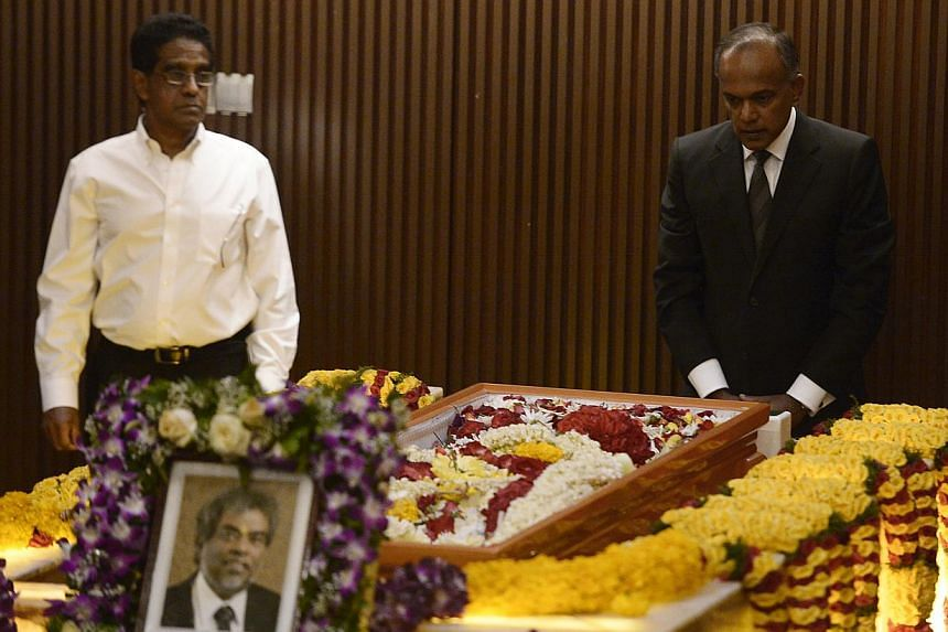 Law Minister K. Shanmugam (right) and lawyer Noor Mohamed Marican (left) paying their respects to the late Subhas Anandan during his funeral held at Mandai Crematorium on 8 Jan, 2015. -- ST PHOTO: MARK CHEONG