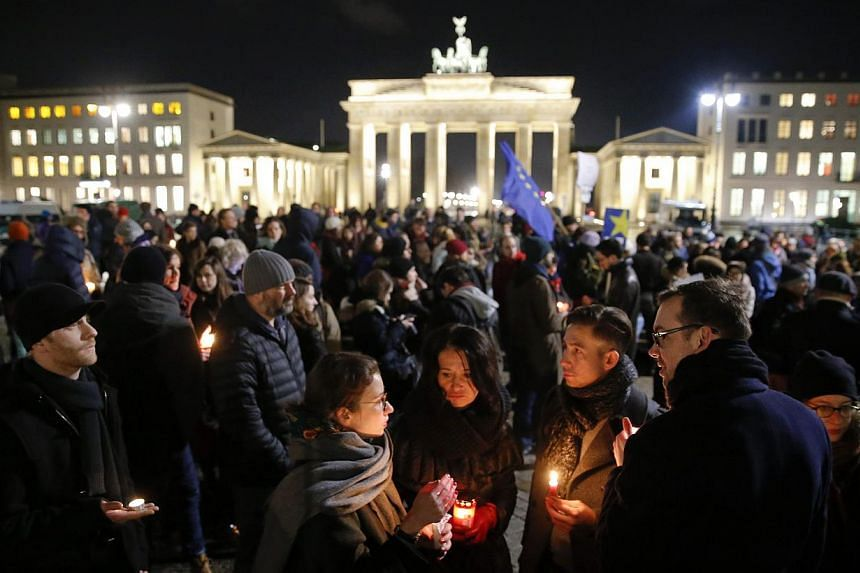 People gathering to mourn for the victims in front of the Brandenburg Gate (centre, background) near the French embassy at Pariser Platz in Berlin Jan 7, 2015, following a shooting by gunmen at the offices of weekly satirical magazine Charlie Hebdo i
