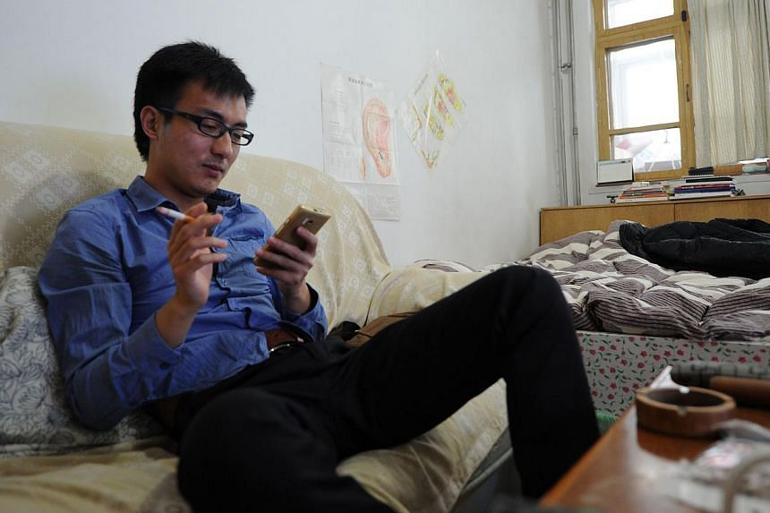 """This picture taken on Dec 15, 2014, shows A Qi using his phone as he smokes in his rented home in Beijing. Mr Zhao Jun, 30, has no girlfriend, no savings and a dull job with bad pay, a typical """"diaosi"""" as they are called, meaning the millions of """"los"""
