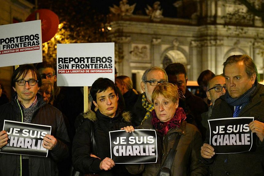 "People holding placards reading ""I am Charlie"" and ""Reporters without borders"" during a gathering in support of the victims of the terrorist attack on French satyrical newspaper Charlie Hebdo, in front of French Embassy in Madrid, Spain on Jan 7, 201"