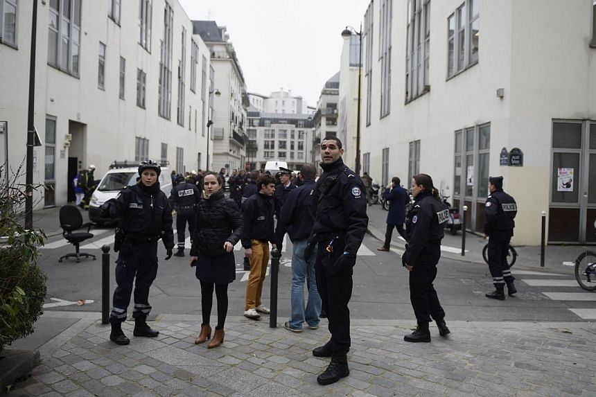 Police forces gather in street outside the offices of the French satirical newspaper Charlie Hebdo in Paris on Jan 7, 2015. The calm, cold determination and deadly efficiency of the gunmen who attacked a French satirical magazine on Wednesday, leavin