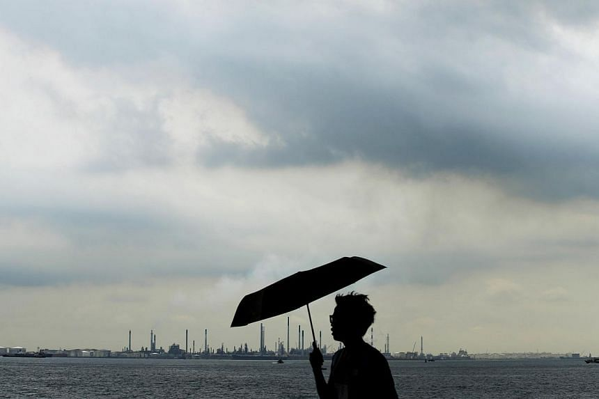 Storm clouds gathering over Shell's Pulau Bukom oil refinery in Singapore on Dec 17, 2014. Oil extended gains in Asia Thursday following a drop in US crude stockpiles. -- PHOTO: REUTERS