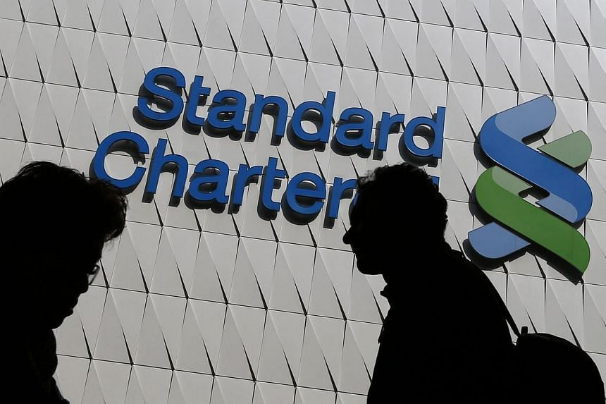 Passersby walk in front of the main branch of Standard Chartered in Hong Kong Jan 8, 2015. Standard Chartered chief executive Peter Sands' decision to cut the bank's loss-making equities business was almost a year in the making, despite the shoc