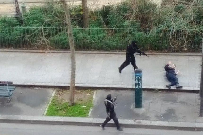 Gunmen flee after shooting a wounded police officer (right) on the ground at point-blank range, outside the offices of French satirical newspaper Charlie Hebdo in Paris, in this still image taken from amateur video shot on Jan 7, 2015, and obtained b