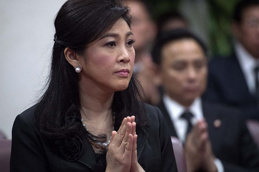 Ousted Thai prime minister Yingluck Shinawatra praying during a funeral ceremony inside a Buddhist temple in Bangkok on Sept 29, 2014. Thailand's legislature will start impeachment hearings this week against Ms Yingluck.