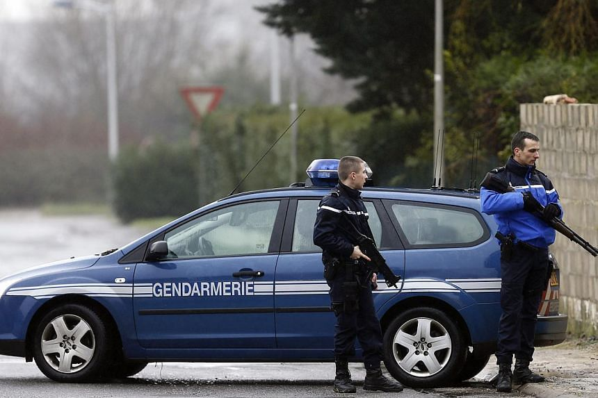 Police officers create a security zone around an industrial area where the suspects in the shooting attack at the satirical French magazine Charlie Hebdo headquarters are reportedly holding a hostage, in Dammartin-en-Goele, some 40 kilometres north-e