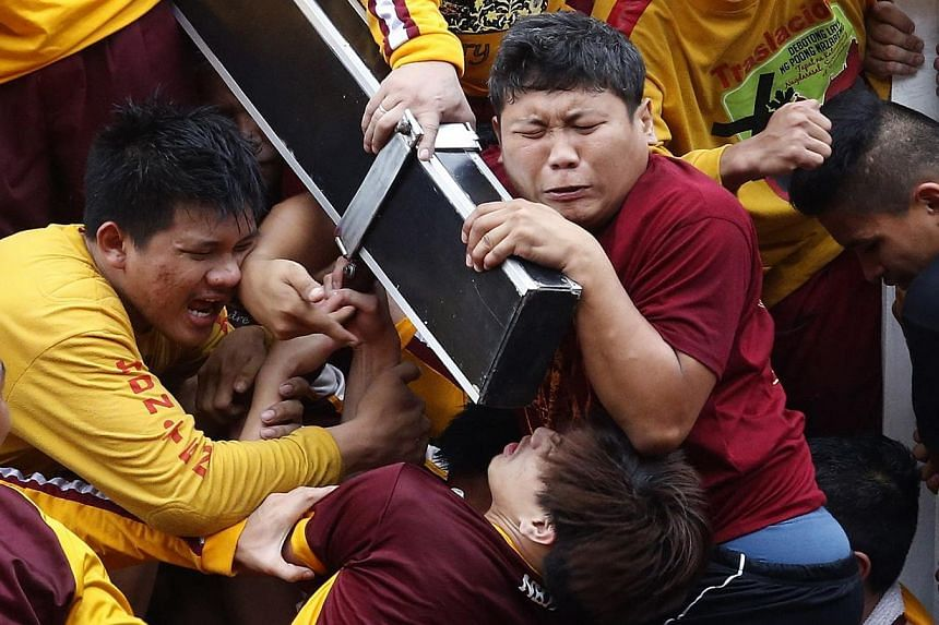 Devotees grimace as they try to hold the Black Nazarene, which is atop a carriage, at the start of an annual procession in Manila, Jan 9, 2015.-- PHOTO: REUTERS