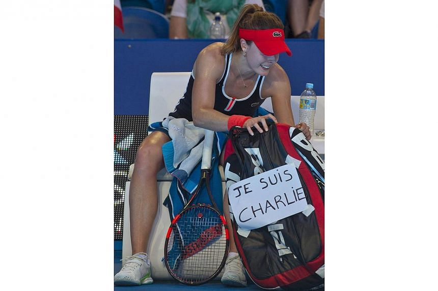 Alize Cornet of France displays a sign on her bag (right) of her support for Charlie Hebdo magazine during a break between games in her match against Agnieszka Radwanska of Poland during their women's singles match on day six of the Hopman Cup tennis